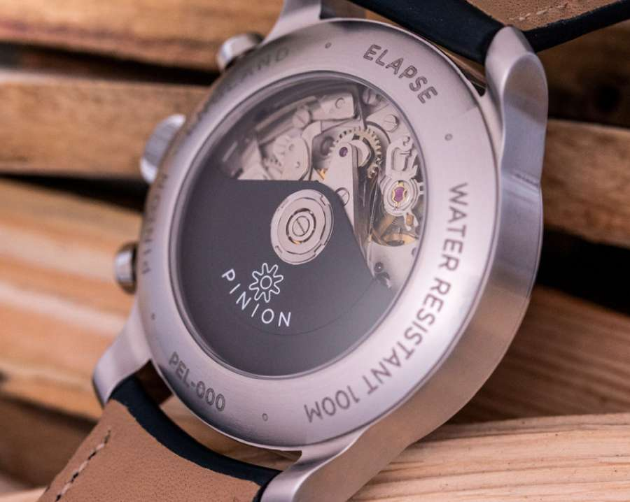 A silver watch on a wooden surface  Description automatically generated with low confidence