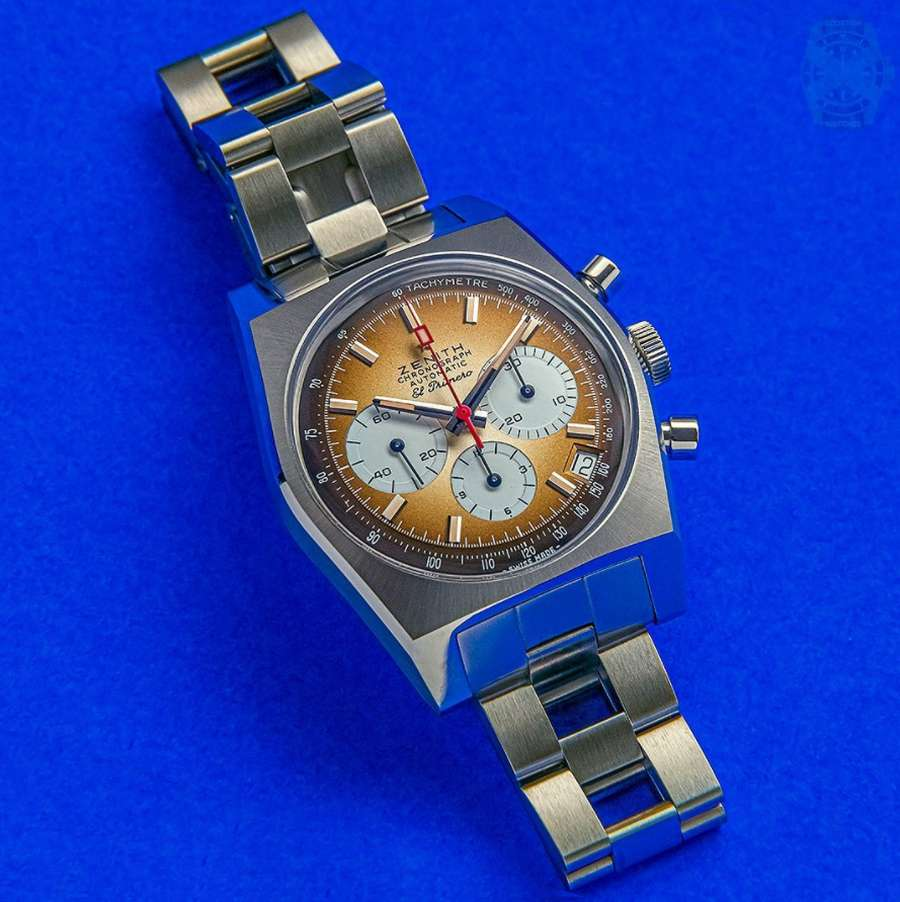 A silver watch on a blue surface  Description automatically generated with low confidence