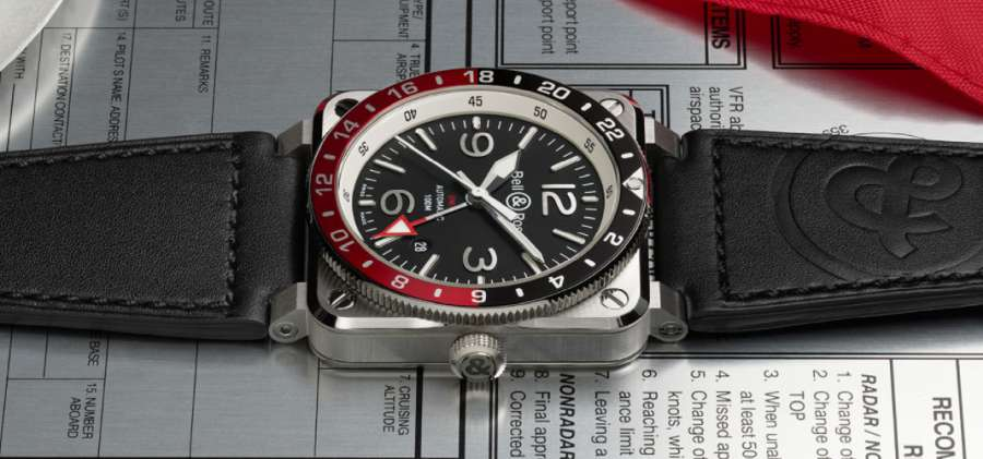 A black and red watch on a white surface  Description automatically generated with low confidence
