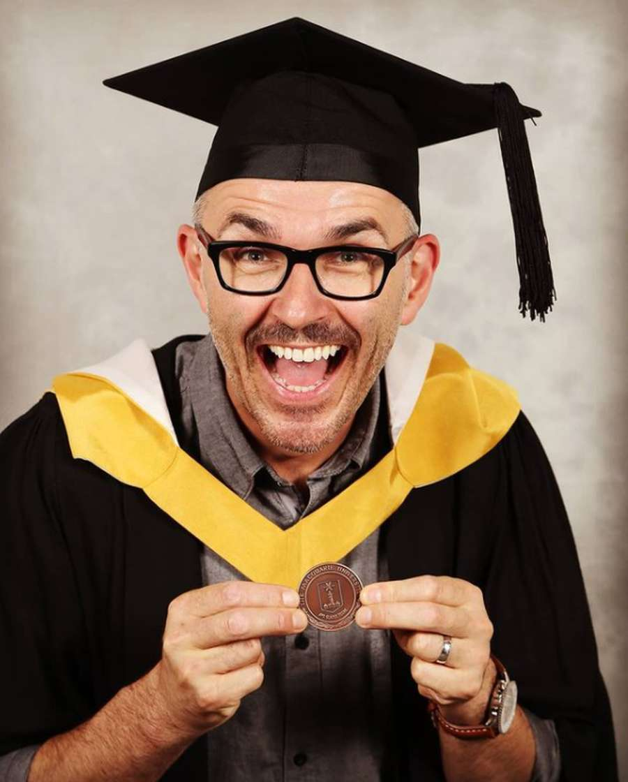 A person wearing a graduation gown and holding a diploma Description automatically generated with low confidence
