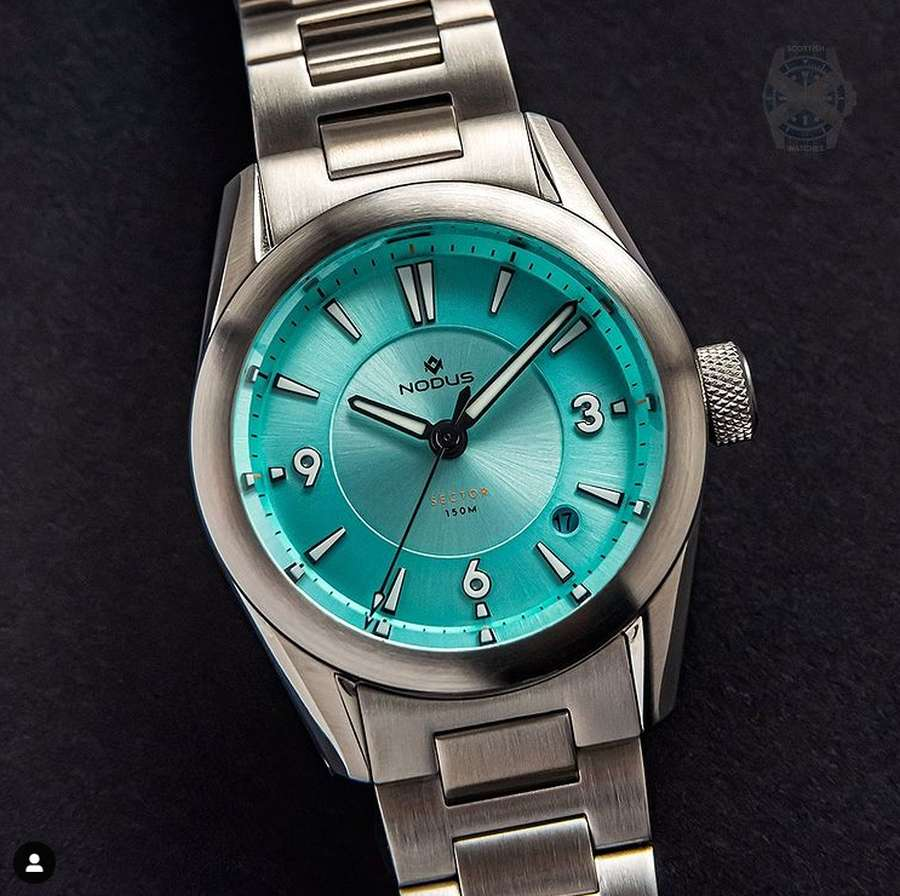 A picture containing watch, attached, close Description automatically generated