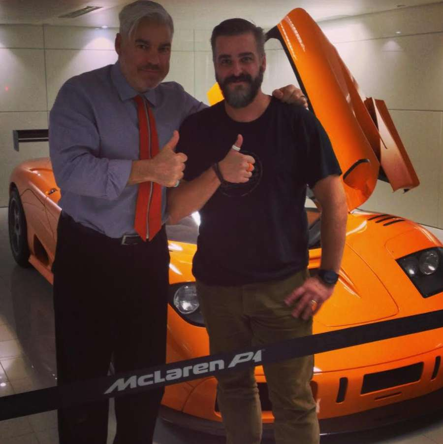 A couple of men posing for a picture next to a sports car Description automatically generated with medium confidence