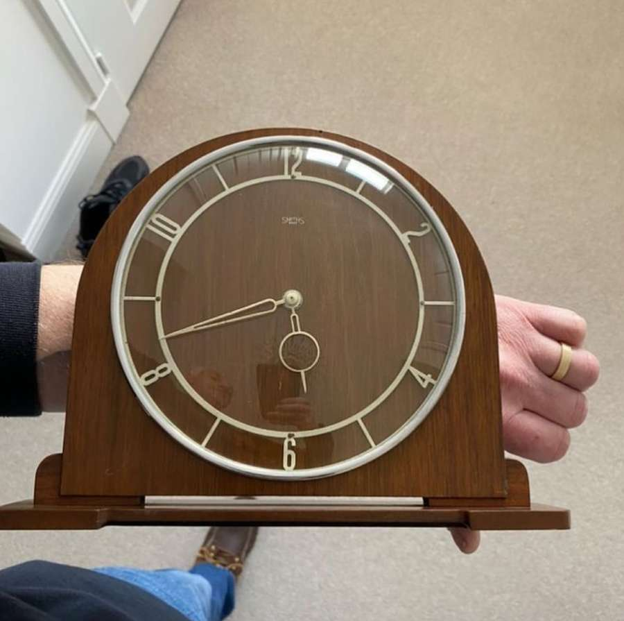 A hand holding a clock Description automatically generated with low confidence